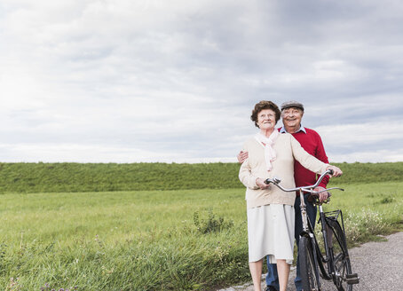 Senior couple with bicycles in rural landscape - UUF12045