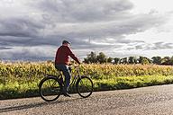 Senior man riding bicycle on country lane - UUF12048