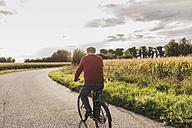 Senior man riding bicycle on country lane - UUF12051