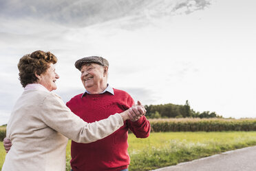 Happy senior couple dancing on country road - UUF12057