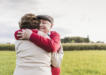 Senior couple hugging in rural landscape - UUF12060