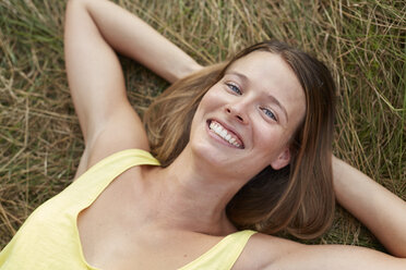 Portrait of laughing young woman lying on a meadow - PNEF00217