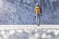 Germany, Berchtesgadener Land, back view of woman with backpack walking on frozen Lake Koenigssee - MMAF00152