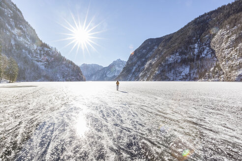 Germany, Berchtesgadener Land, back view of woman with backpack standing on frozen Lake Koenigssee - MMAF00155