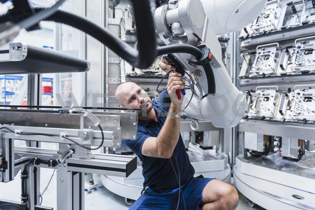 Man working at industrial robot in modern factory - DIGF02931 - Daniel Ingold/Westend61