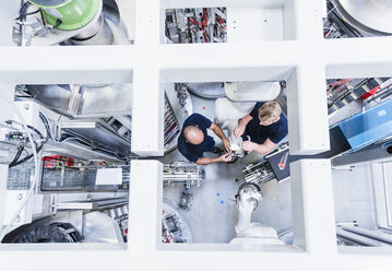 Top view of two colleagues working at industrial robot in modern factory - DIGF02949