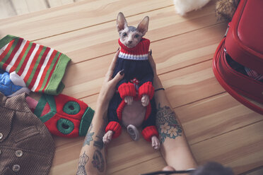 Close-up of woman holding Sphynx cat wearing pullover - RTBF01062