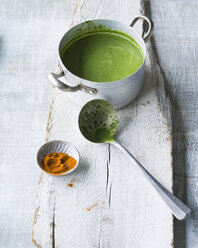 Pot of spinach soup and soup ladle on wood - PPXF00120