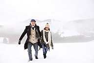 Portrait of happy senior couple walking in snow-covered landscape - HAPF02228