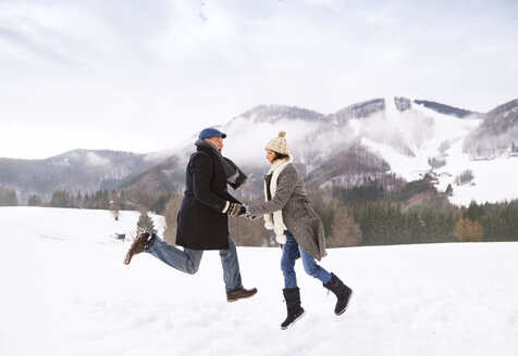 Happy senior couple jumping in the air in snow-covered landscape - HAPF02231