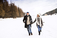 Happy senior couple walking in snow-covered landscape - HAPF02234