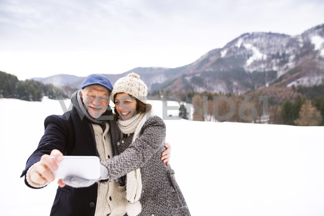 Senior couple kissing taking selfie with cell phone in winter landscape - HAPF02237