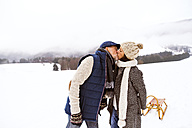 Kissing senior couple with sledge in snow-covered landscape - HAPF02246