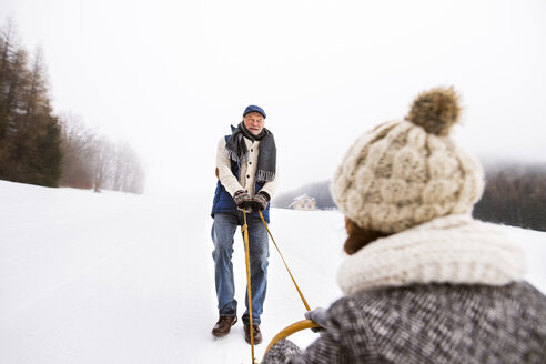 Happy senior couple having fun with sledge in snow-covered landscape - HAPF02249