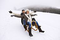 Senior couple having fun with sledge walking in the snow - HAPF02252