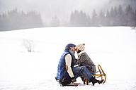 Happy senior couple sitting face to face on sledge in winter landscape - HAPF02255
