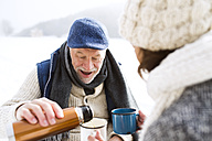 Senior couple having a break with hot beverages in snow - HAPF02258