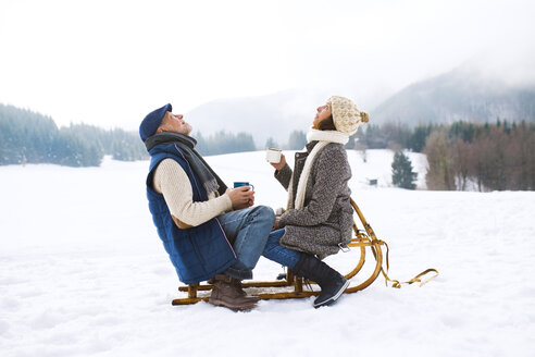 Senior couple sitting on sledge with hot beverages in snow-covered winter landscape looking up - HAPF02261