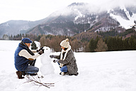 Senior couple building up snowman in winter landscape - HAPF02267