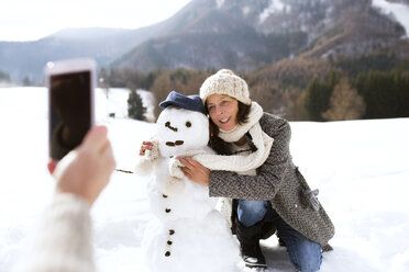 Senior man taking picture of his wife with snowman - HAPF02270