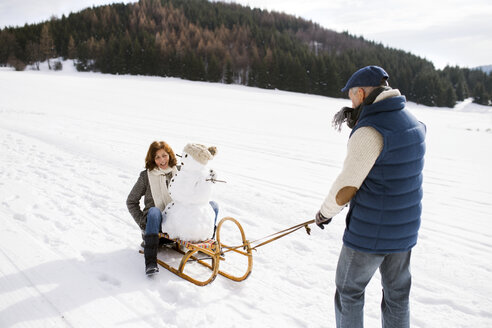 Senior couple with snowman on sledge in winter landscape - HAPF02273