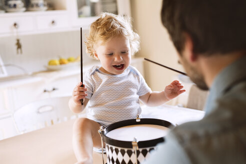 Father with happy little boy sitting on kitchen table playing drum - HAPF02285