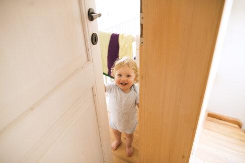 Portrait of happy baby boy opening the door - HAPF02288