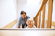 Father with little boy on wooden stairs at home - HAPF02291
