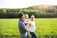 Parents walking with little boy on meadow - HAPF02306
