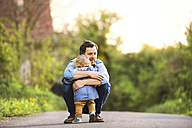Father hugging little boy on field path - HAPF02309
