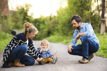 Cute little boy with parents on field path - HAPF02312