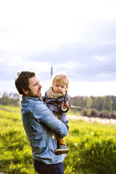Father holding cute little boy with twig - HAPF02315