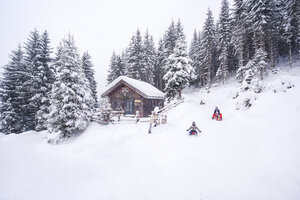 Austria, Altenmarkt-Zauchensee, family tobogganing at wooden house at Christmas time - HHF05493
