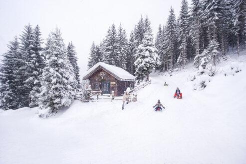 Austria, Altenmarkt-Zauchensee, family tobogganing at wooden house at Christmas time - HHF05493