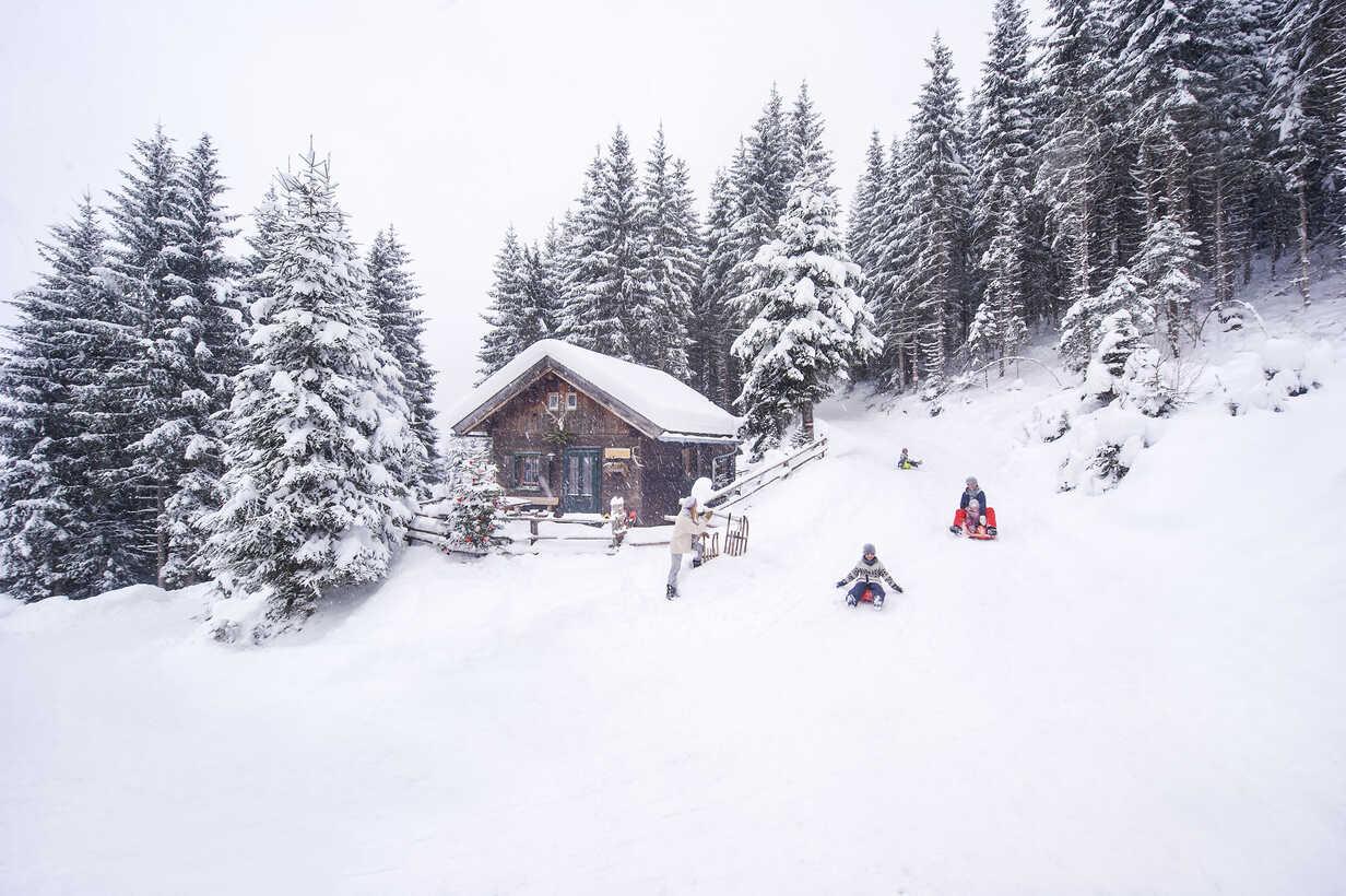 Austria, Altenmarkt-Zauchensee, family tobogganing at wooden house at Christmas time - HHF05493 - Hans Huber/Westend61