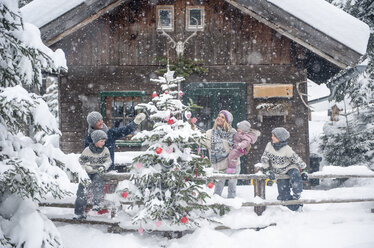 Austria, Altenmarkt-Zauchensee, family decorating Christmas tree at wooden house - HHF05496