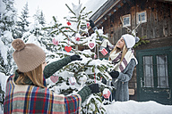 Austria, Altenmarkt-Zauchensee, two young women decorating Christmas tree at wooden house - HHF05500