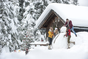 Austria, Altenmarkt-Zauchensee, friends building up big snowman at wooden house - HHF05503