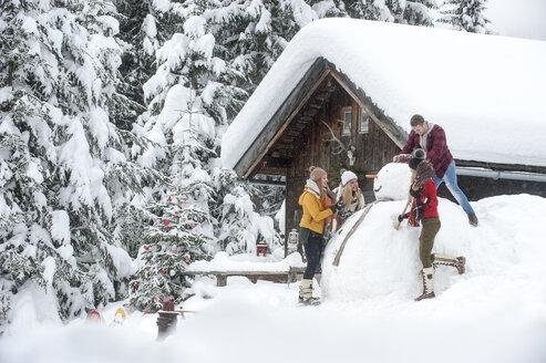 Austria, Altenmarkt-Zauchensee, friends building up big snowman at wooden house - HHF05503