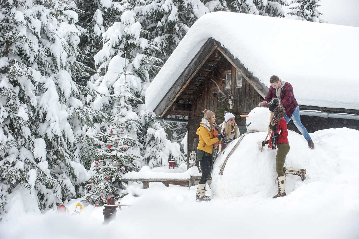 Austria, Altenmarkt-Zauchensee, friends building up big snowman at wooden house - HHF05503 - Hans Huber/Westend61