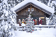 Austria, Altenmarkt-Zauchensee, friends decorating Christmas tree at wooden house - HHF05506