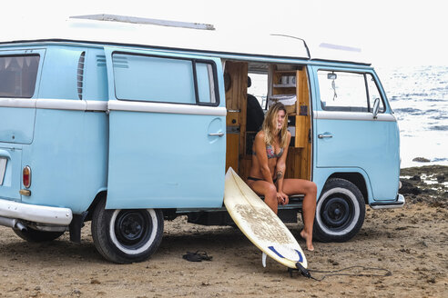 Portrait of happy young woman with surfboard in van on the beach - SIPF01799