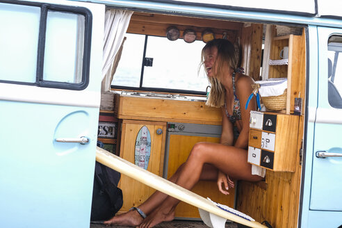 Laughing young woman with surfboard in van - SIPF01802