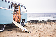 Laughing young woman with surfboard in van on the beach - SIPF01805