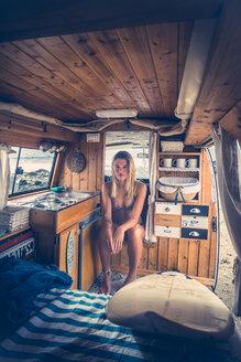 Young woman in bikini sitting in mobile home - SIPF01808