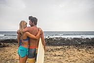 Young couple with surfboard standing on the beach - SIPF01814