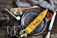 Grilled corncob with butter, salt and chili flakes on plate - SBDF03341