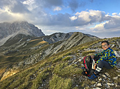 Italy, Abruzzo, Gran Sasso, Hiker resting in the mountains - LOMF00635