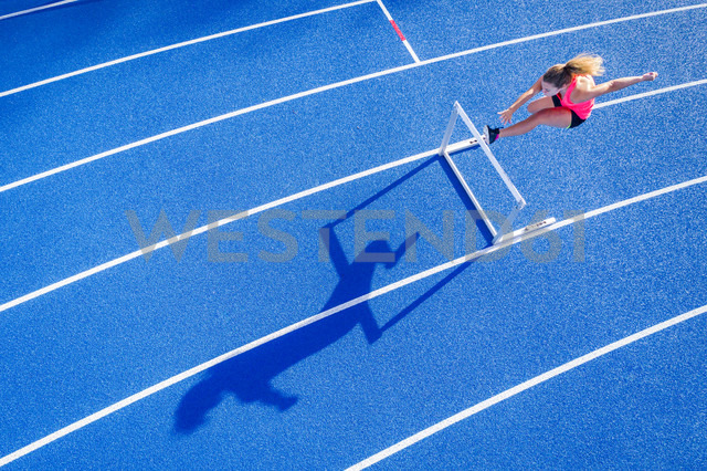 Top view of female runner crossing hurdle on tartan track - STSF01331 - Stefan Schurr/Westend61