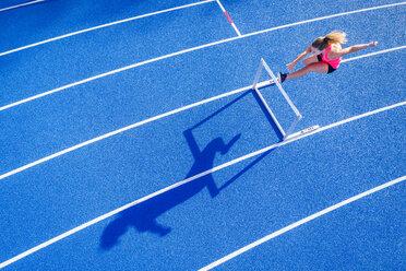 Top view of female runner crossing hurdle on tartan track - STSF01331
